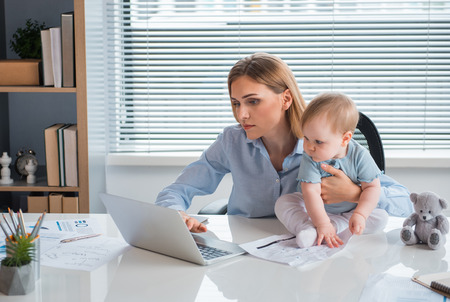 Portrait of serene businesswoman typing in laptop. interested baby looking at it while locating on desk in apartment. Labor and family concept