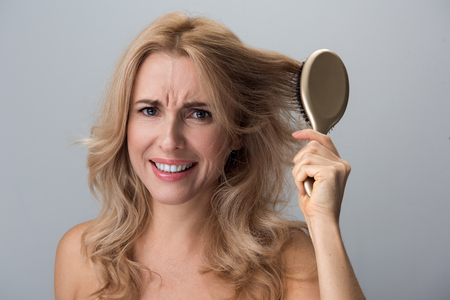 Haircare concept. Portrait of dissatisfied middle-aged woman trying to comb her long hair. She is looking at camera and frowning her face while feeling pain. Isolated background