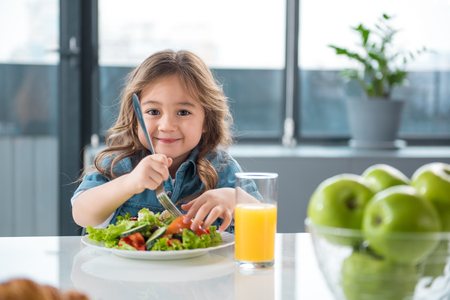 Portrait of pretty little female child having healthy breakfast. She is holding fork under the chopped vegetables and smiling Foto de archivo