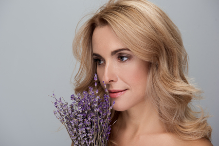 Close-up of face of attractive middle-aged elegant blond woman is enjoying aroma of lavender flowers while standing with naked shoulders and looking aside thoughtfully. Isolated background