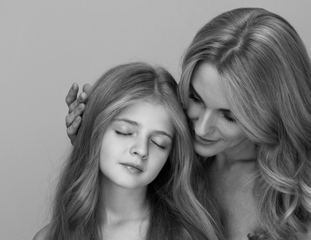 Tenderness. Portrait of delightful little daughter with closed eyes is standing with her gorgeous mother. woman is gently touching head of child. Black and white with isolated background