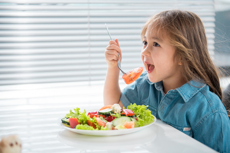 Side view of hungry asian girl eating piece of tomato with appetite. She is sitting at table in kitchen Archivio Fotografico