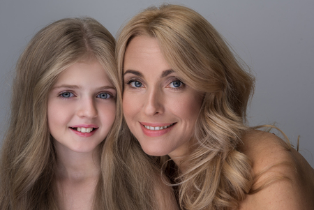 Family time. Portrait of cheerful charming elegant mother and adorable little daughter are looking at camera with joy while posing with naked shoulders. Isolated background
