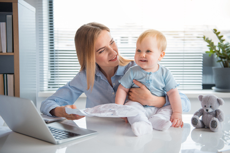 Portrait of outgoing mom showing paper to happy kid while working at table in modern office. Occupation and child concept Zdjęcie Seryjne