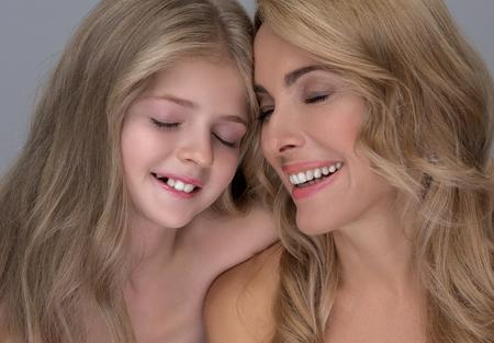 Mejor momento. Adorable pequeña hija está abrazando tiernamente a su hermosa madre de mediana edad. Están de pie con los ojos cerrados mientras expresan felicidad. Fondo aislado Foto de archivo