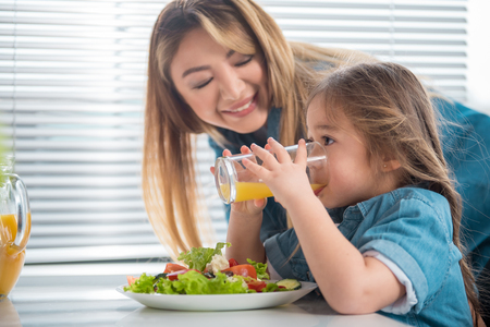 Side view profile of pretty little girl drinking orange juice with concentration. Her mom is looking at kid with love and smiling while standing in kitchen Stock Photo