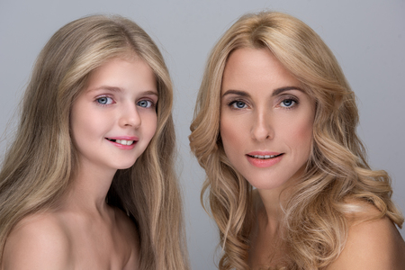 My pride. Portrait of optimistic attractive elegant mother and adorable little daughter are standing with naked shoulders while looking at camera with joy. Isolated background Standard-Bild