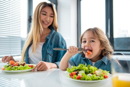 Portrait of hungry little girl eating fresh chopped vegetables with appetite. She is looking at camera and smiling. Her mom is sitting at table next to the child