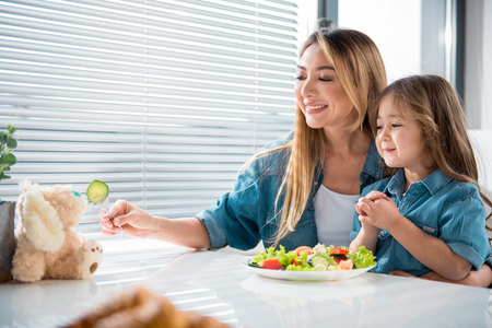 Your little puppy likes healthy food too. Cheerful mother is stretching fork with piece of cucumber to toy while her daughter is looking at it with admiration. Playful eating concept Stock Photo - 91544345