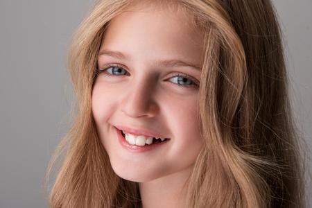 행복한 미소. 쾌활 한 매력적인 소녀의 근접 초상화 얼굴 서 고 기쁨을 함께 카메라를 찾고. 고립 된 배경