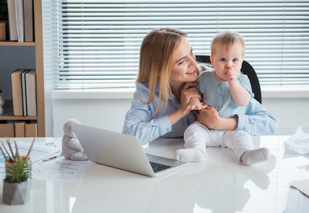 Portrait of smiling mother telling with calm kid. He keeping finger in mouth while locating on desk. Occupation and family concept Zdjęcie Seryjne