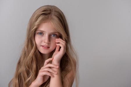 ポジティブかわいい女の子の肖像画は、彼女の顔に触れながら、笑顔でカメラを見て立っています。右側にコピースペースを持つ分離された背景