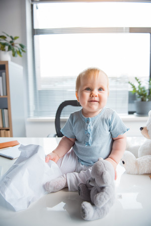 Portrait of smiling baby playing with toys while locating on desk in modern office. Kid at work concept