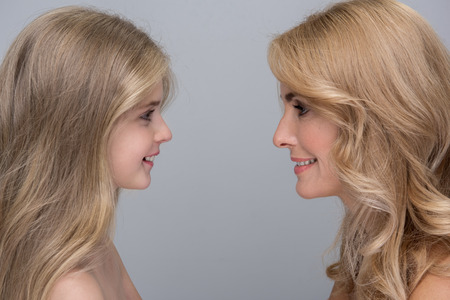 My little princess. Side view profile of cheerful mother and her pretty daughter are standing and looking at each other with love. They are feeling happiness while spending time together. Isolated Banque d'images