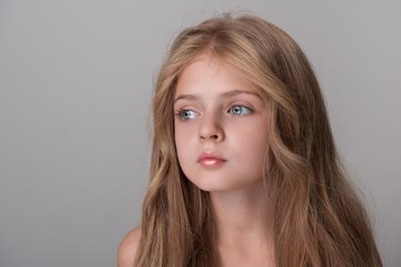 Eenzaam voelen. Het serieuze meisje staat weemoedig opzij. Geïsoleerde achtergrond Stockfoto - 91545054