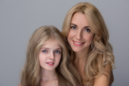 We are family. Portrait of positive elegant mother and loveable little daughter are standing with naked shoulders and looking at camera with smile. Isolated background