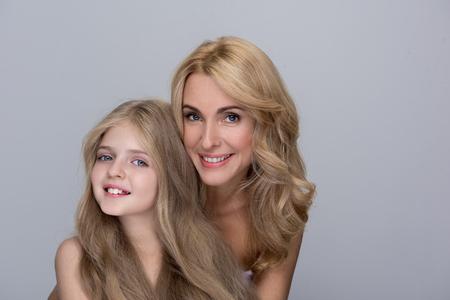 사랑의 포옹. 사랑스러운 작은 딸과 뒤에 서 있고 사랑을 evincing 동안 웃 고 그녀의 매력적인 어머니의 초상화. 고립 된 배경 스톡 콘텐츠
