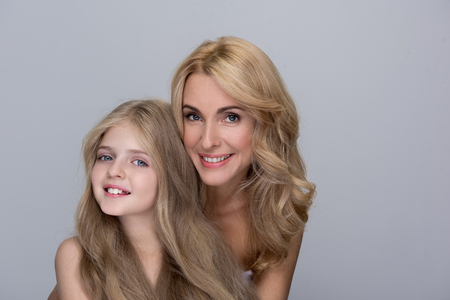Câlins aimants. Portrait de l'adorable petite fille et de sa charmante mère qui se tient derrière et sourit en faisant preuve d'amour. Arrière-plan isolé Banque d'images - 91545286