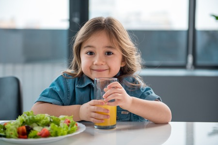 Waist up portrait of happy asian girl drinking fresh orange juice in the kitchen. She is looking at camera and smiling