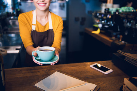 Here is your order. Close up arms of outgoing girl keeping cup of delicious hot tea while standing at counter in cafe. Job concept Stock Photo