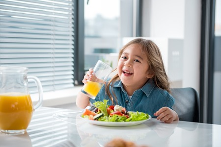Portrait of pretty asian girl drinking healthy juice with pleasure. She is laughing while sitting at table near plate of salad Stock Photo