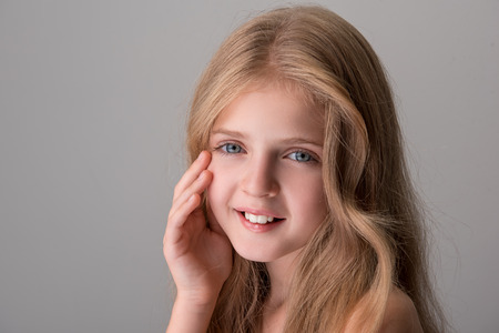 Young and beautiful. Portrait of joyful pretty little girl with long hair and naked shoulders is standing and looking at camera with smile while touching her face. Isolated background with copy space Archivio Fotografico