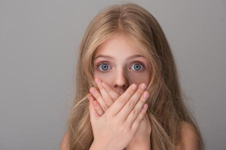 Il ritratto del primo piano della bambina scioccata con capelli lunghi e le spalle nude sta esaminando la macchina fotografica con gli occhi spalancati mentre copriva la sua bocca a mano. Sfondo isolato