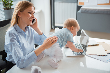 Side view beaming young mom taking care of kid. He creeping on desk. Cheerful woman telling by phone. Profession and child concept