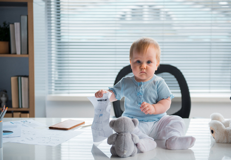 Full length portrait of serious small child holding document while playing on desk in modern office. Job and baby concept Stock Photo