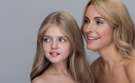 Joyful attractive mother and her adorable little daughter are standing together with naked shoulders while looking aside with smile. Isolated background Foto de archivo