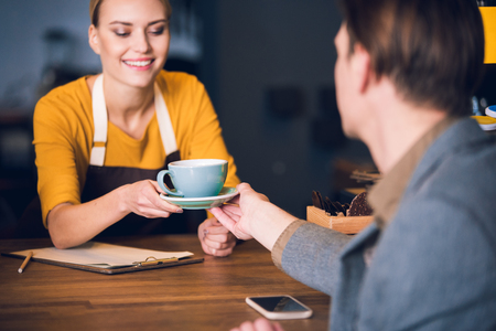 Outgoing woman worker giving cup of delicious tea to visitor in cozy cafe. Job concept