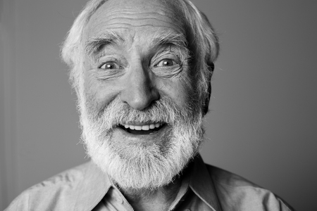 Sincere amazement. Close up black-and-white portrait of aged happy pensioner with widely open eyes while standing. Isolated on grey background 写真素材