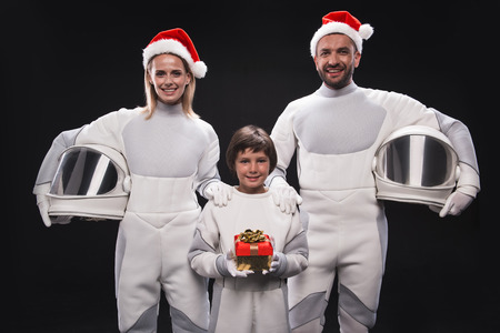 Christmas in space concept. Portrait of cheerful family of astronauts in red hats are standing and holding helmets while looking at camera with smile. Cute boy is standing with gift box. Isolated