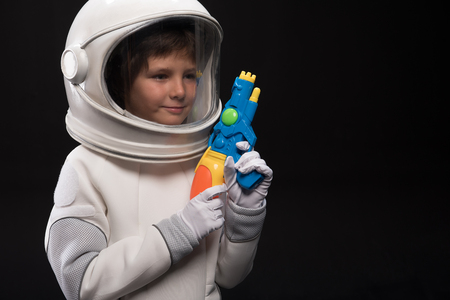 Protector. Positive little astronaut wearing white helmet with full armor is standing and holding space blaster while looking aside with slight smile. Isolated with copy place in the right side