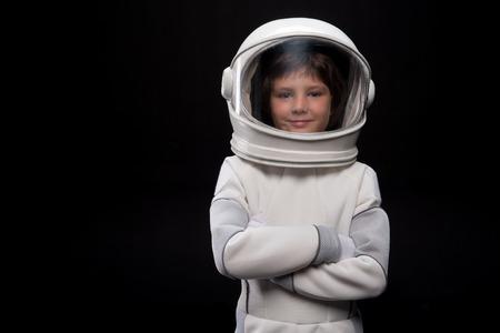 우주 비행사 개념입니다. 허리 위로 흰색 기갑을 입고 긍정적 인 작은 소년의 초상화와 헬멧 카메라와 함께 기쁨을 찾고있는 동안 팔을 교차 서있다.