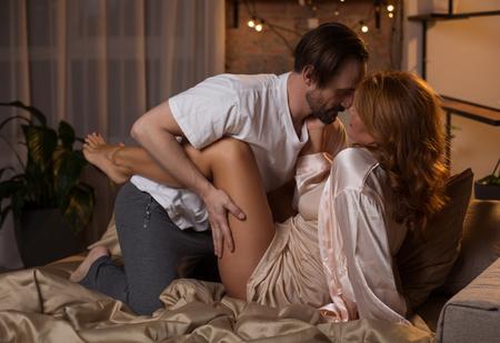 Zijaanzicht van gepassioneerd verliefde paar van middelbare leeftijd knuffelen terwijl liggend op bed. De mens raakt vrouwelijk been terwijl hij zijn wens uitdrukt Stockfoto