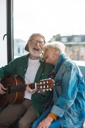 Merry aged man and woman spending holiday while playing on guitar and singing at home. Portrait Banco de Imagens