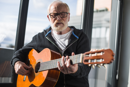 Waist up portrait of mature male pensioner sitting at window and enjoying calm sounds of musical instrument