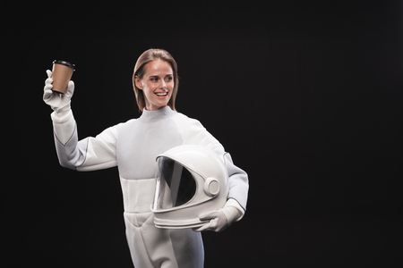 Best beverage. Cheerful young charming spacewoman wearing protective suit is enjoying hot coffee. She is looking aside with wide smile while standing and holding helmet. Isolated with copy space