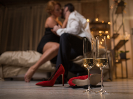 Focus on two glasses of champagne on floor. Ardent loving couple is sitting on bed and hugging with passion on background. Romantic date concept Stock Photo