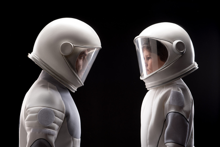 Side view profile of qualified astronaut father and his small son are standing and looking at each other seriously. They are posing in helmet and protective suit. Isolated background Foto de archivo
