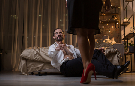 Come to me. Middle-aged man is sitting on floor and stretching hand to woman with desire. Focus on female legs standing on high heels Stock Photo