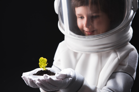 Discovering new forms. Close-up of hands with green plant of happy little astronaut wearing helmet and protective suit who is standing and feeling interest. Isolated background. Selective focus Stock Photo