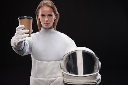 Serious young trained female cosmonaut is stretching coffee to camera while holding helmet and standing confidently. Isolated background. Selective focus