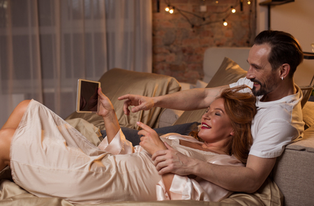 Side view of happy middle-aged couple watching video on tablet and laughing. They are lying on bed with relaxation
