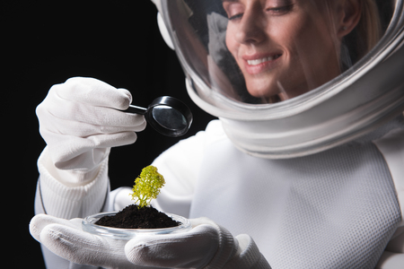 Cheerful female cosmonaut researcher wearing helmet is standing and looking through magnifier on green plant on her palm while expressing gladness and curiosity. Selective focus. Isolated. Close-up Stock Photo - 91857775