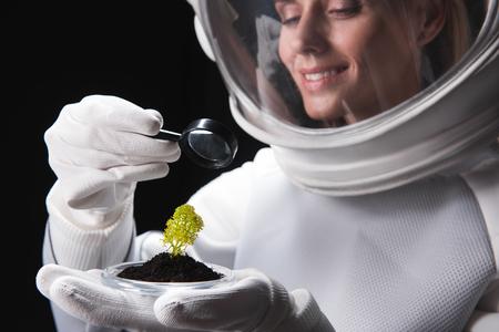Il casco d'uso del ricercatore femminile allegro del cosmonauta sta stando e guardando attraverso la lente sulla pianta verde sulla sua palma mentre esprime la gioia e la curiosità. Messa a fuoco selettiva. Isolato. Avvicinamento Archivio Fotografico - 91857775