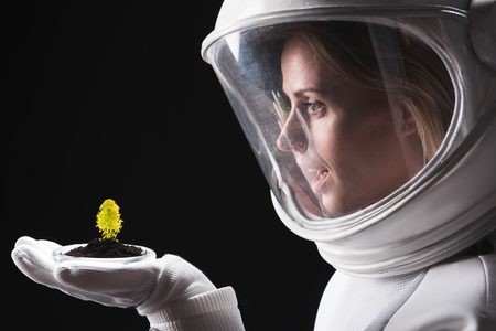 Feeling wonder. Close-up profile of amazed female astronaut is standing in helmet and holding on palm new form of green plant. She is expressing astonishment while looking at it. Isolated background Foto de archivo