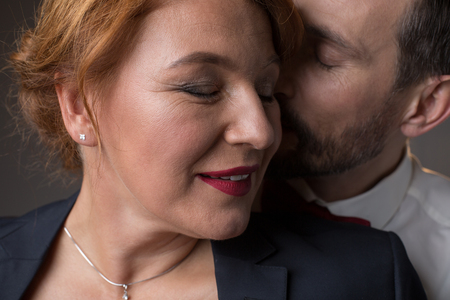 Close up of happy woman face smiling while man is kissing her cheek with gentleness 写真素材