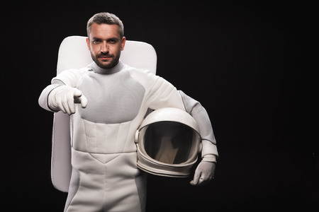 You. Portrait of confident spaceman is standing and pointing on you while looking at camera seriously. He is holding helmet while posing in astronaut protective suit. Isolated with copy space Фото со стока
